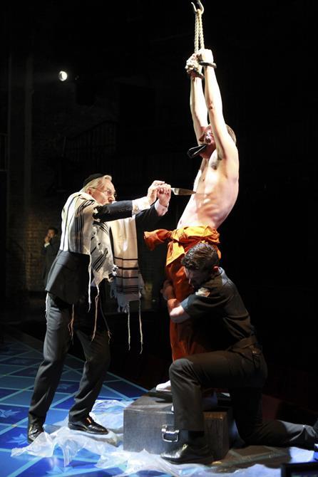 Shylock prepares to take a knife to Antonio's chest.