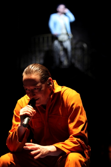 Production image of Antonio (Scott Handy) using a microphone.