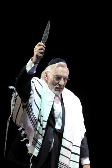 Shylock (Patrick Stewart) raising his dagger.