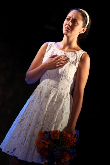 Portia (Susannah Fielding) hand on chest, clutching a bunch of flowers.