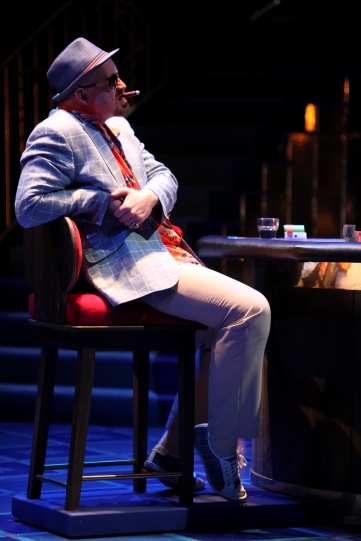 Solanio (Aidan Kelly) smoking a cigar at the casino table.