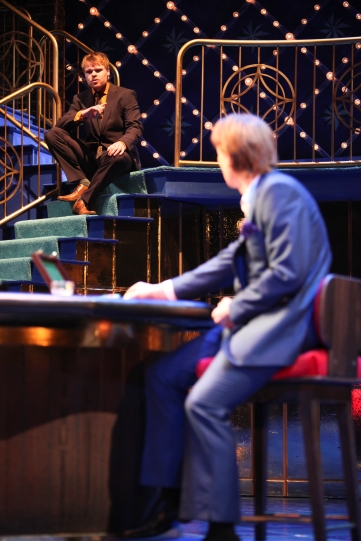Bassanio (Richard Riddell) sat on stairs talking to Antonio (Scott Handy).