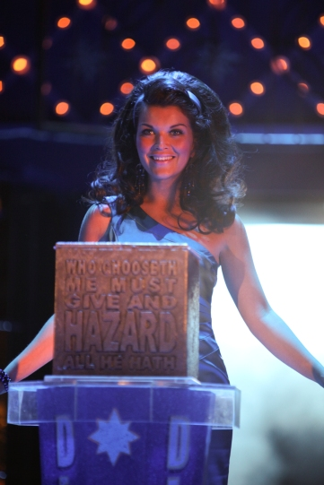 Nerissa (Emily Plumtree) with a slate with the quote 'Who chooseth me must give and hazard all he hath'.