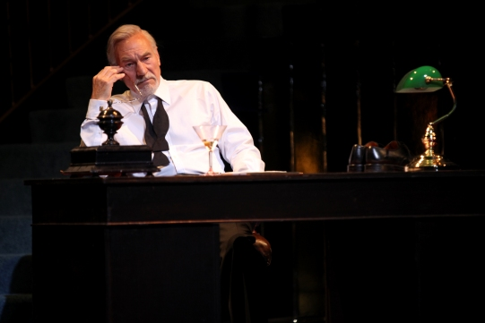 Shylock (Patrick Stewart) sat at a table deep in thought.