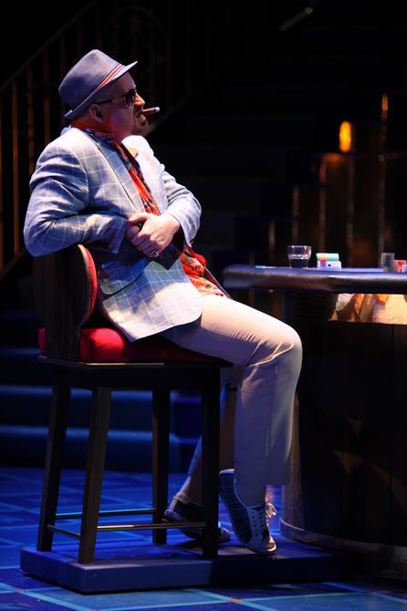 Solanio smoking a cigar at the casino table.