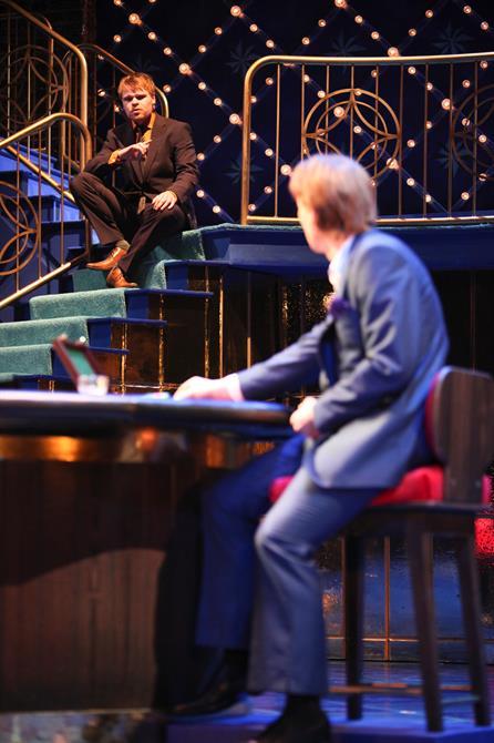 Bassanio (Richard Riddell) sat on stairs talking to Antonio (Scott Handy).