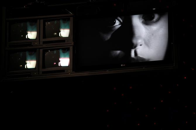 Production image of 5 CCTV screens, the large one showing a black and white close up of a woman's face.