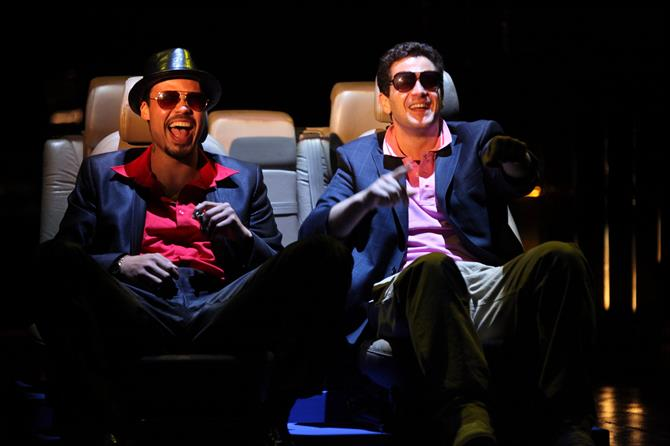 Gratiano (Howard Charles) and Lorenzo (Daniel Percival) wearing sunglasses, seated and laughing.