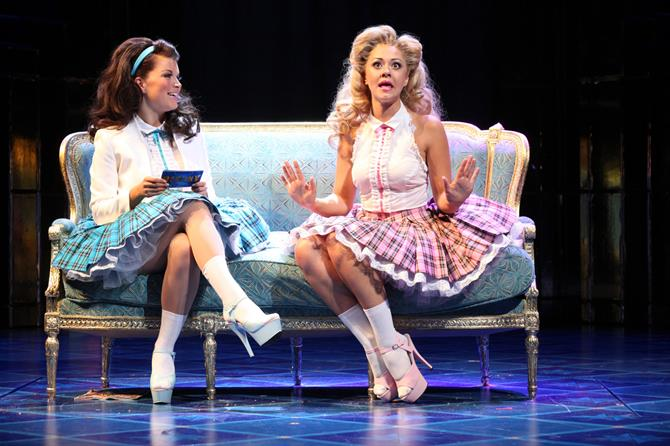 Portia (Susannah Fielding) and Nerissa (Emily Plumtree) talking on a sofa in checked twill skirts.