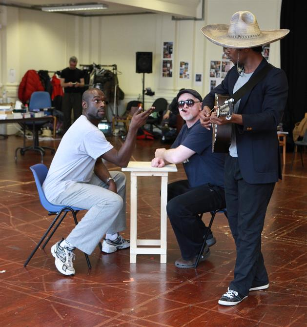 A man in a sombrero plays the guitar to two men seated at a table.