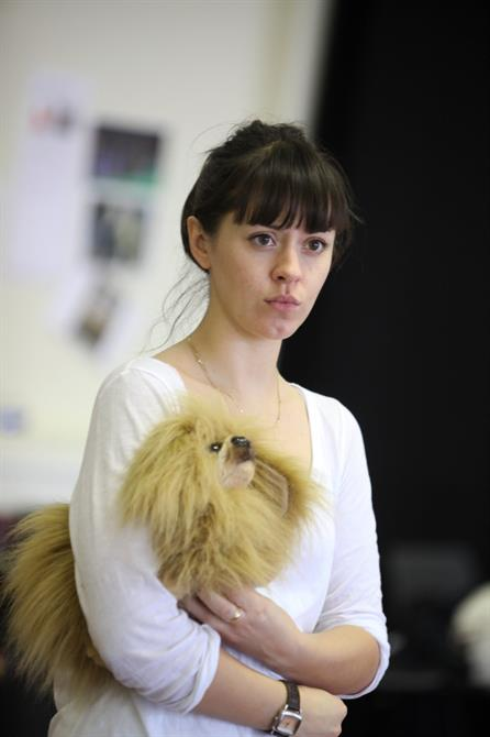 A woman holding a toy dog under her arm.