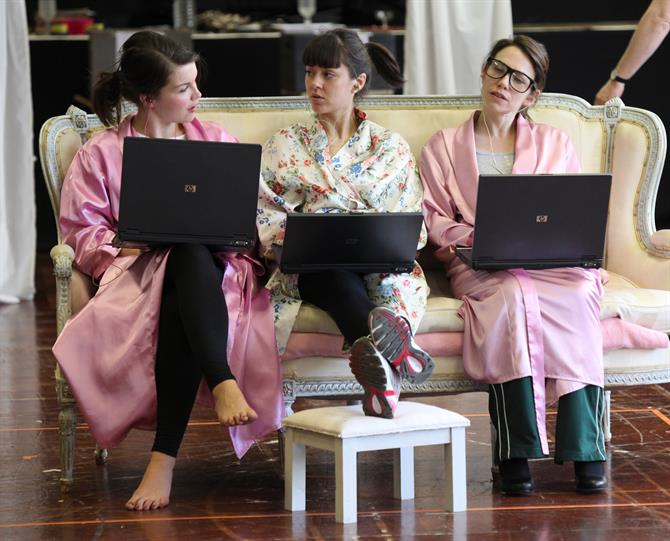 Three women in bedclothes sit on a sofa with laptops on their laps.