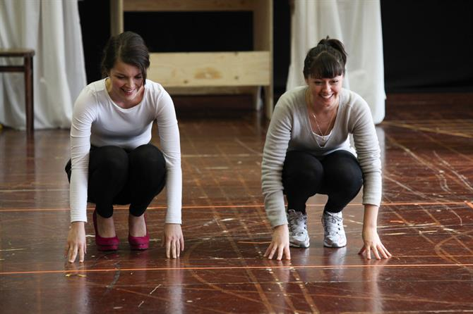 Two women crouch down with their hands resting on the floor.