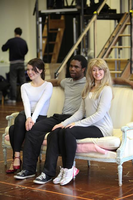 A man sits between two women on a white sofa.
