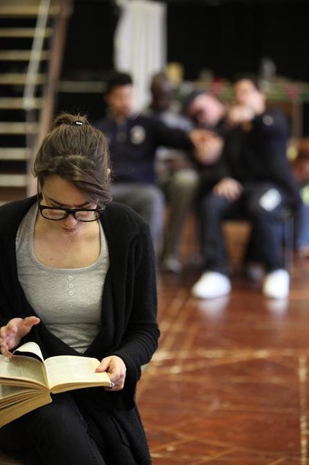A woman in glasses sits reading a book.