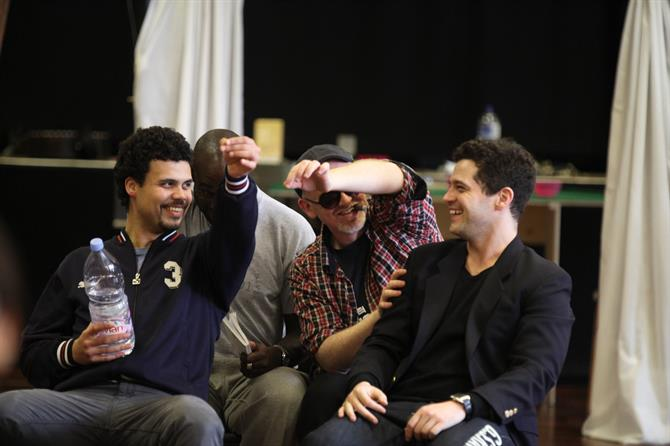 A group of four men, sitting and laughing.