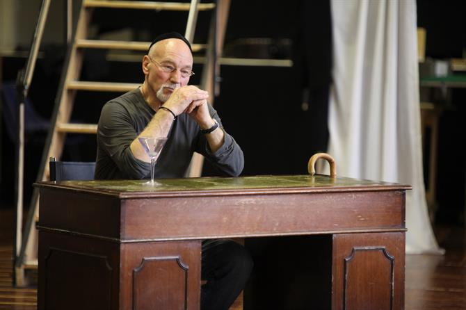 Patrick Stewart as Shylock, sitting pensively behind a wooden desk.