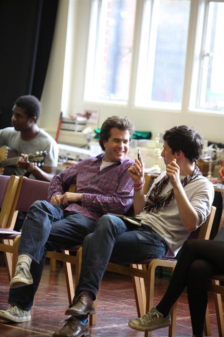 Two men sit talking in rehearsals.
