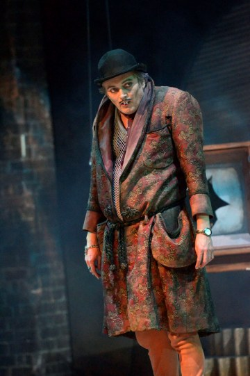 Michael Hodgson as Manny, with hunched shoulders, pointed front teeth and grubby clothing