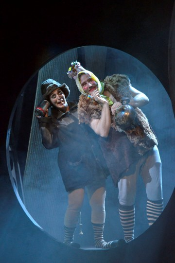 Actors dressed as Rats in a tunnel, wearing stripy socks and bizarre headdresses