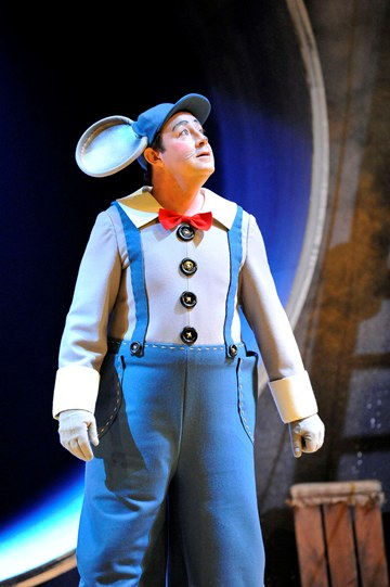 Daniel Ryan as Mouse, wearing blue dungarees and a cap with large mouse ears