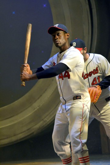 baseball player dressed in white holding a bat up ready to strike