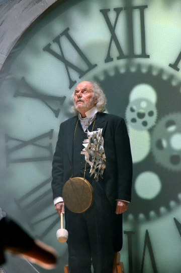 David Sterne with a gong around his neck, in front of a projection of an old-fashioned clock face
