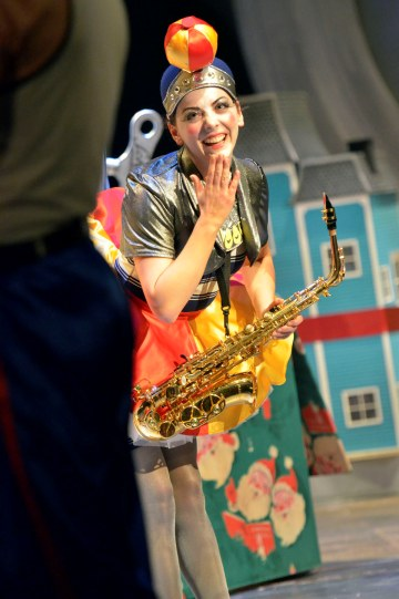 Naomi Sheldon as Seal, carrying a saxophone