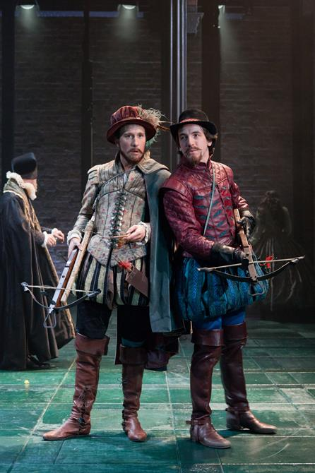 Production image of Ross Armstrong as Scott and Jamie Wilkes as Hammon, holding crossbows.