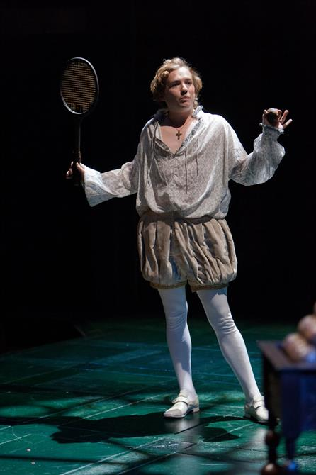 Production image of Jack Holden as The King, holding a racket.