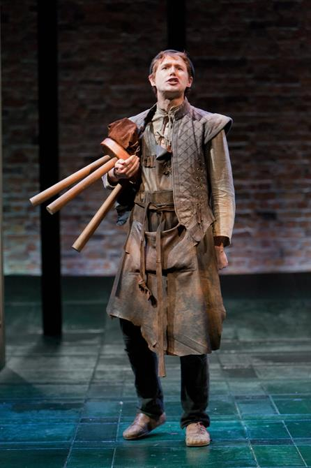 Production image of Joel MacCormack as Firk clutching a brown stool in The Shoemaker's Holiday.