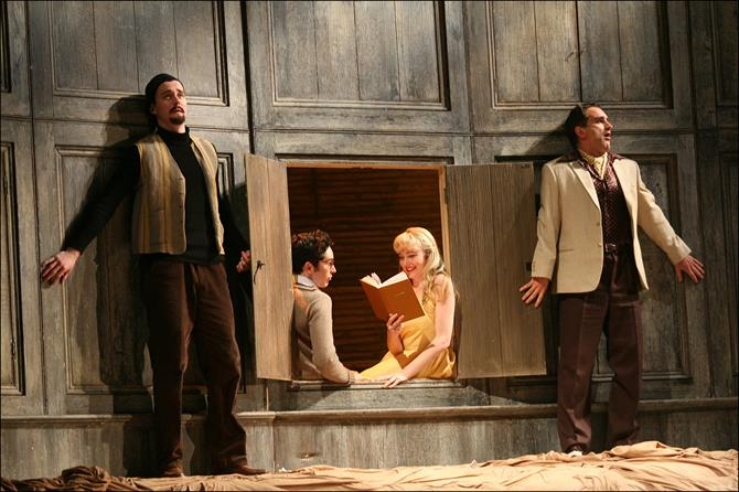 Two men press themselves against the wall as they eavesdrop on a woman reading to a man.