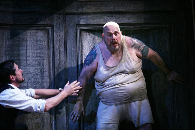 A man in a dirty vest looks fearful as another man raises his arms towards him.