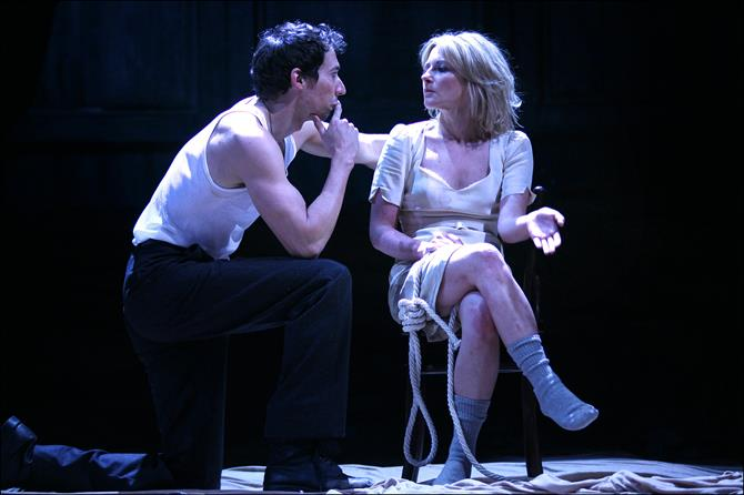 A man crouches to the side of a woman with rope around her.