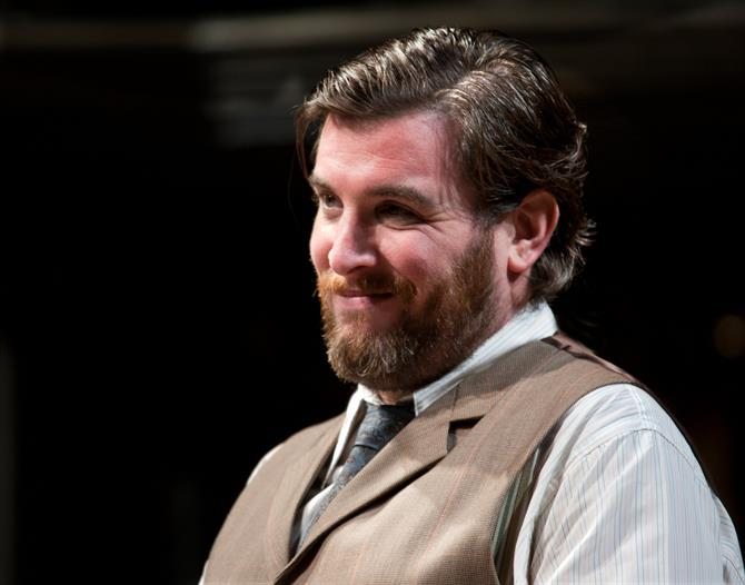 Simon Yadoo as Panthino, wearing a shirt, tie and a vest, smiling