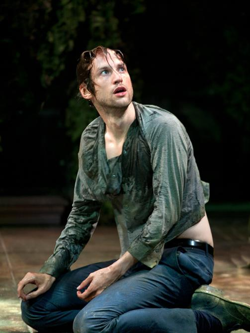 Mark Arends as Proteus, kneeling in a creased up green shirt, his hair wet