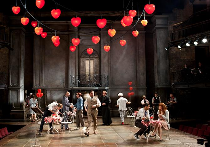 The stage decorated with heart shaped balloons, with cafe-style tables and chairs. There are people sitting and walking around