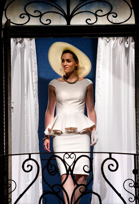 Sarah MacRae as Silvia wearing a modern white dress, pearls and a wide hat
