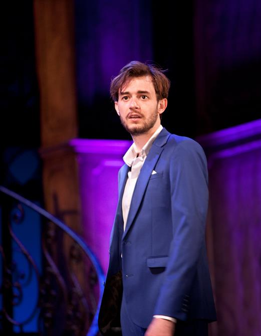 Michael Marcus as Valentine, wearing a blue suit, standing against a dark background lit up by pink and purple lights