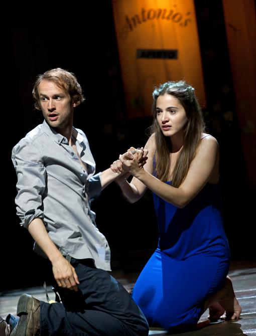 Proteus and Julia kneeling on the floor, clutching each other's hands. Julia is wearing a blue dress and Proteus in a loose shirt