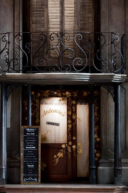A close look of the exterior of Antonio's restaurant with a decorated doorway, a blackboard menu and a balcony above