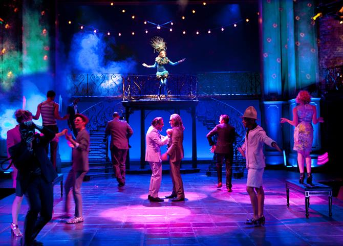 Milan disco scene in The Two Gentlemen of Verona 2014, the stage lit by blue and purple lights and the cast dancing