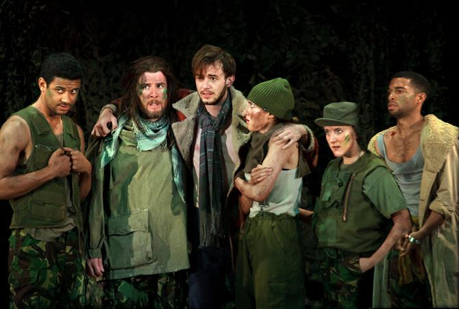 Valentine with his arms around the outlaws, who are all wearing camouflage green clothes and face paint