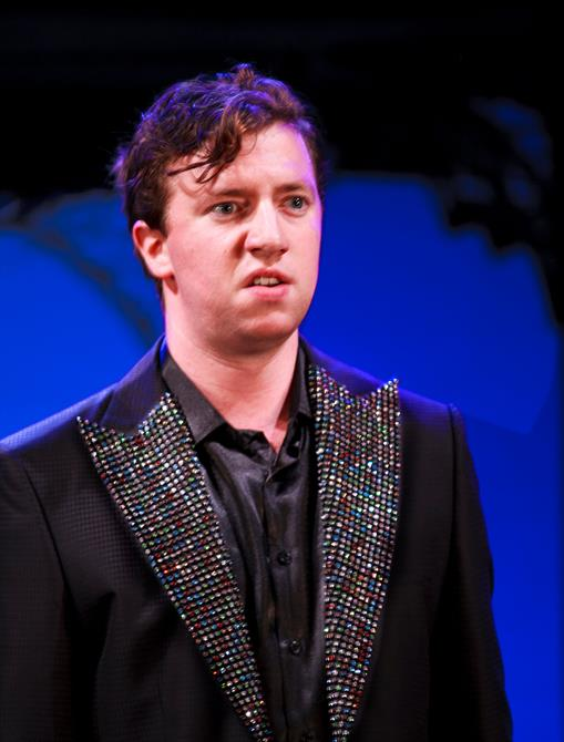 Nicholas Gerard-Martin as Turio, wearing a sparkling black suit, looking mildly disturbed