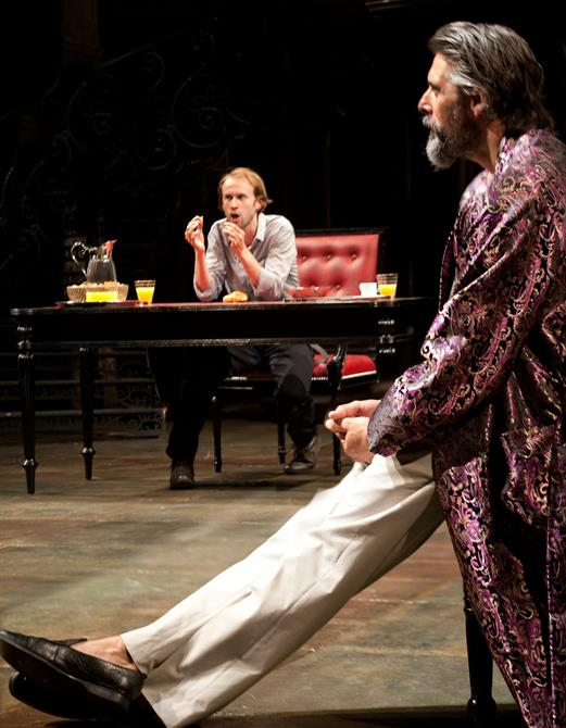 Proteus sitting at a desk, talking animatedly and the duke of Milan sitting at the side in a colourful robe