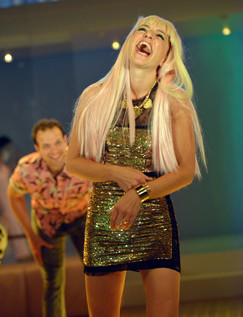 A laughing woman with long blonde hair wears a short shiny green dress