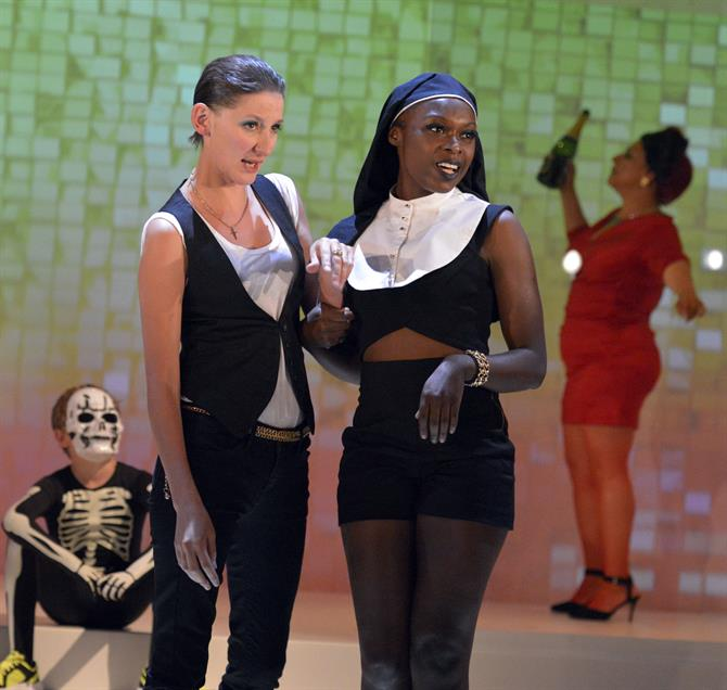 Laura Elphinstone as Flaminio, wearing a white t-shirt and a vest, standing next to a girl in a short and tight nun costume