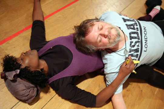 Rakie Ayola and Duncan Wisbey lie on the floor with their eyes closed