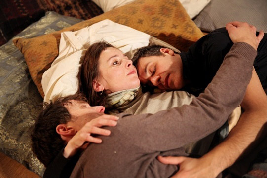 Jo Stone-Fewings, Tara Fitzgerald and Adam Levy lie on cushions on the floor with their arms around each other