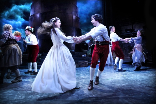 A bride in white dances energetically with a man in a white shirt and red trousers.